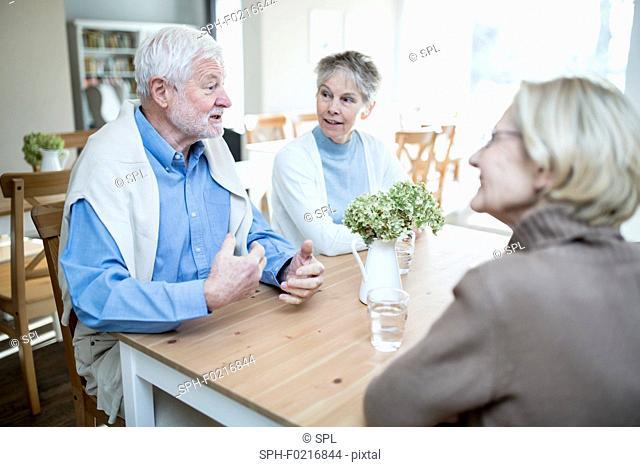 Senior man talking to two female friends