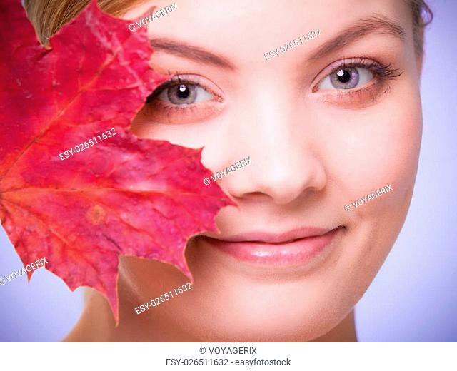 Skincare habits. Portrait of young woman with leaf as symbol of red capillary skin on violet. Face of girl taking care of her dry complexion