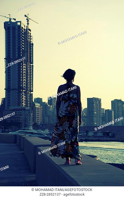 Rear view of a woman wearing a summer dress standing against the skyline