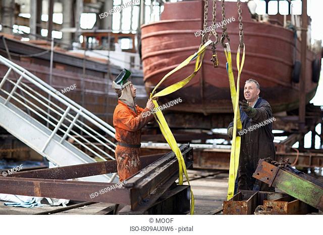 Workers using winch for girders in shipyard workshop