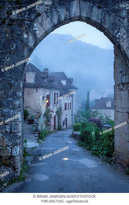 Misty dawn at the entry gate to Saint Cirq Lapopie, Lot Valley, Midi-Pyrenees, France