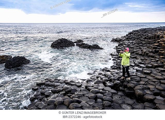 Young woman taking pictures of the basalt rocks, Giant Causeway, Coleraine, Northern Ireland, United Kingdom, Europe