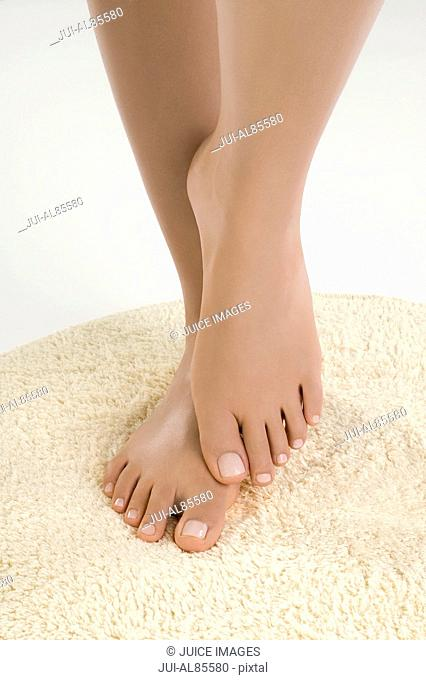 Close up of woman's bare feet on rug