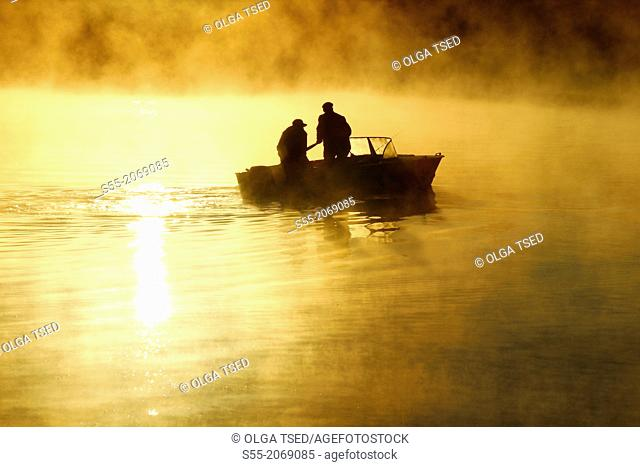 Two fishermen in the Finnish Gulf, sunrise. Primorsk, Russia