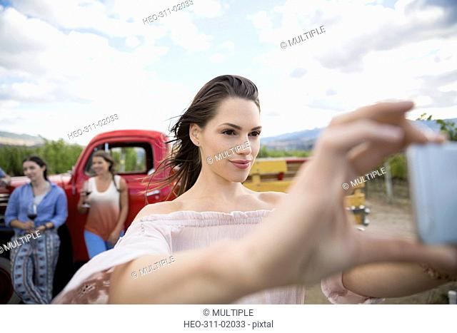 Woman with camera phone taking selfie in vineyard