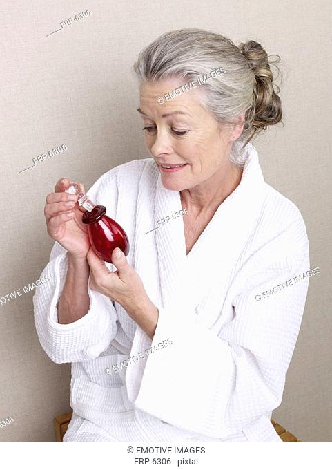 Senior woman holding perfume bottle