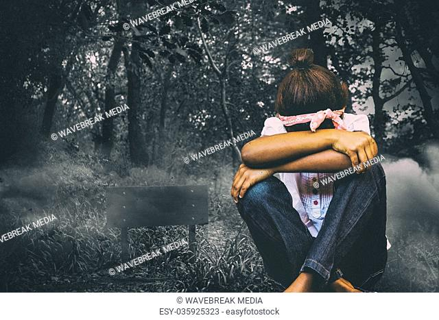 Composite image of tensed girl sitting against brick wall in school corridor