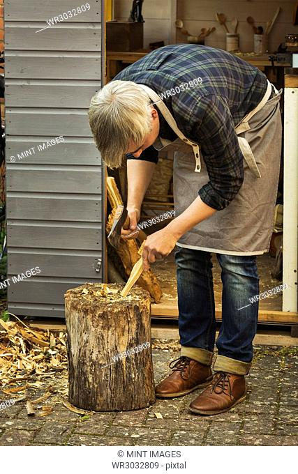 Craftsman woodcarver bending down and holding a hand axe, cutting a small piece of wood on a splitting block