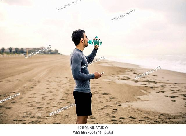 Sportive young man drinking from bottle on the beach