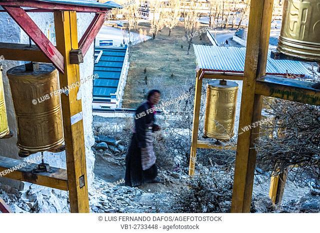 Tibetan pilgrim and prayer wheels at Tashilhunpo Monastery, Shigatse, Tibet