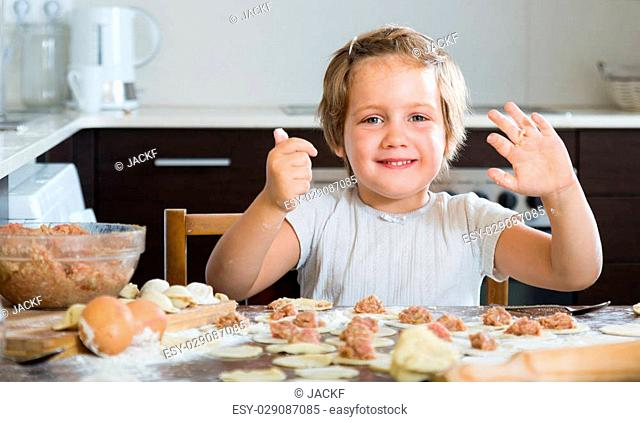 Smiling little girl making fish dumplings from meat stuffing and dough at home kitchen