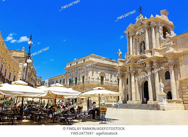 Piazzo del Duomo, Ortygia, Syracuse, Sicily with the baroque faceade of the Church of Santa Lucia alla Badia opposite a local cafe restaurant
