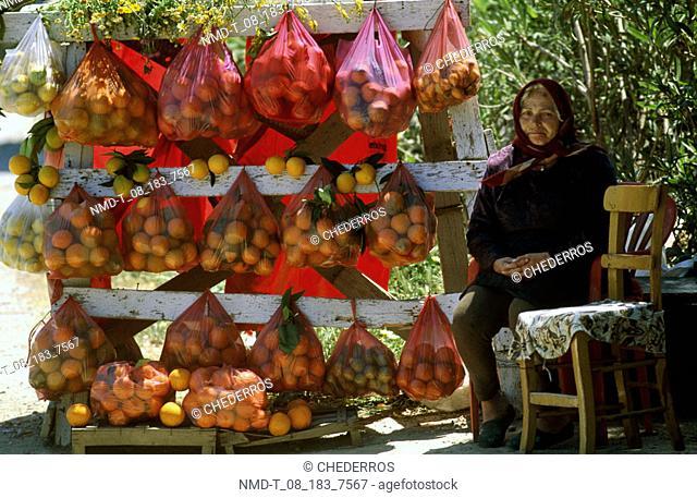 Senior woman sitting besides a fruit shop, Crete, Greece