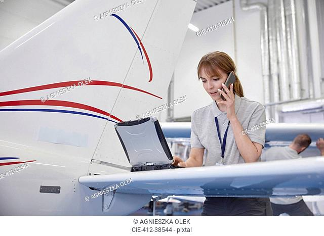 Female airplane engineer working at laptop and talking on cell phone in hangar