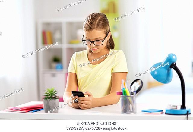 student girl with smartphone doing homework