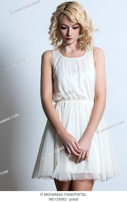 Sad young woman in hwite dress