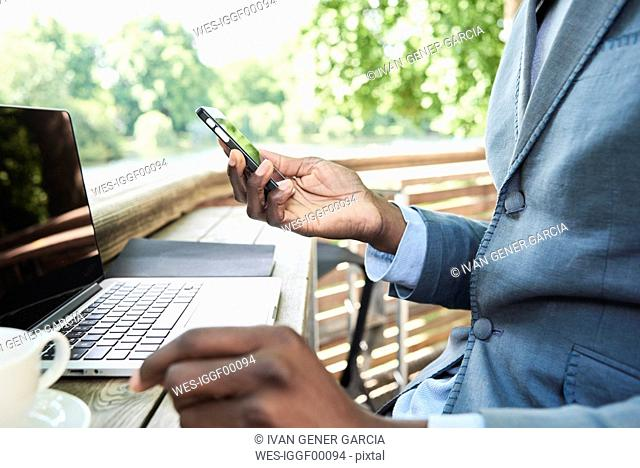 Businessman checking phone while working on his laptop on a terrace, partial view