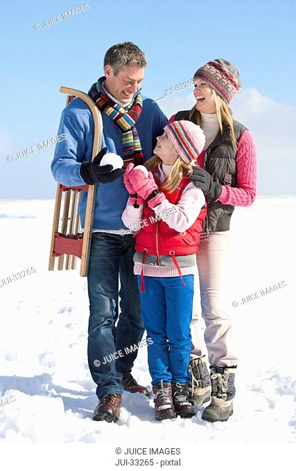Smiling parents and daughter with snowball and sled in snow