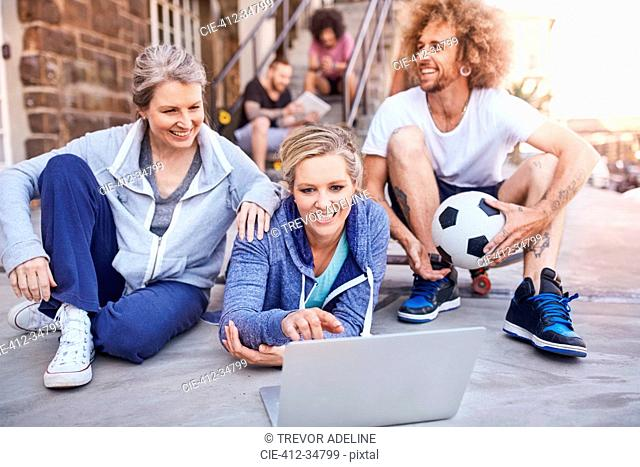 Friends with soccer ball hanging out using laptop