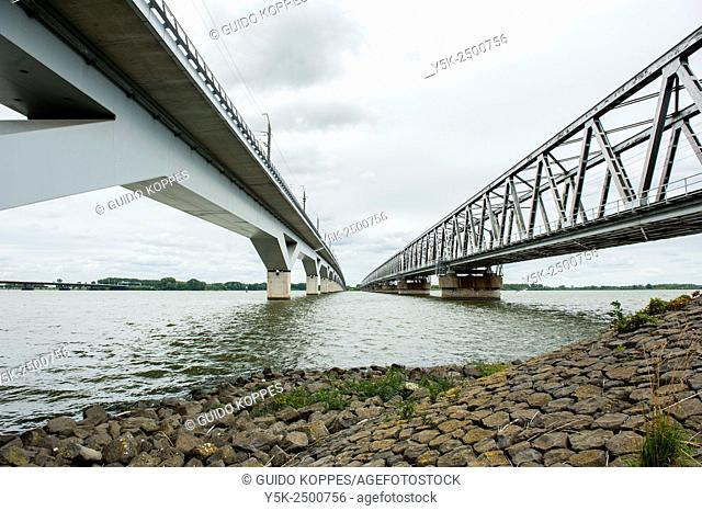 Moerdijk, Netherlands. One 1950's build rail road bridge, besides a newly build high speed rail road bridge crossing the river Hollandsch Diep