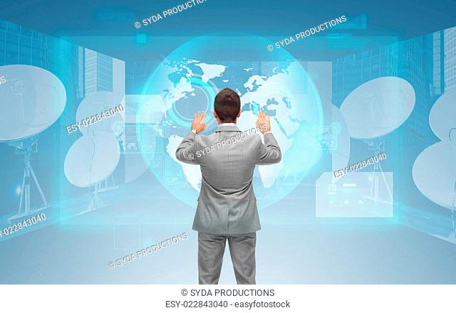 business, people, global network and technology concept - businessman touching virtual screen with world map and satellite antennas over blue background from...