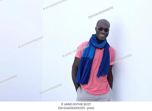 Man wearing scarf and sunglasses, smiling, portrait
