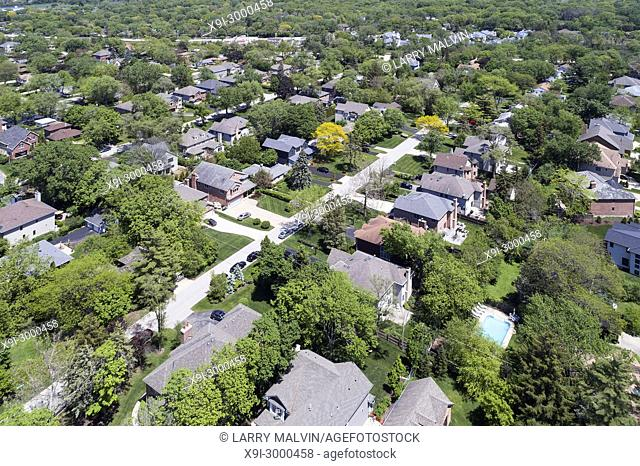 Aerial view of a neighborhood with mature trees in a Chicago suburban neighborhood in summer. Deefield, IL. USA