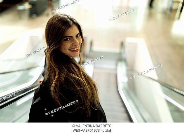 Portrait of smiling young woman on escalator