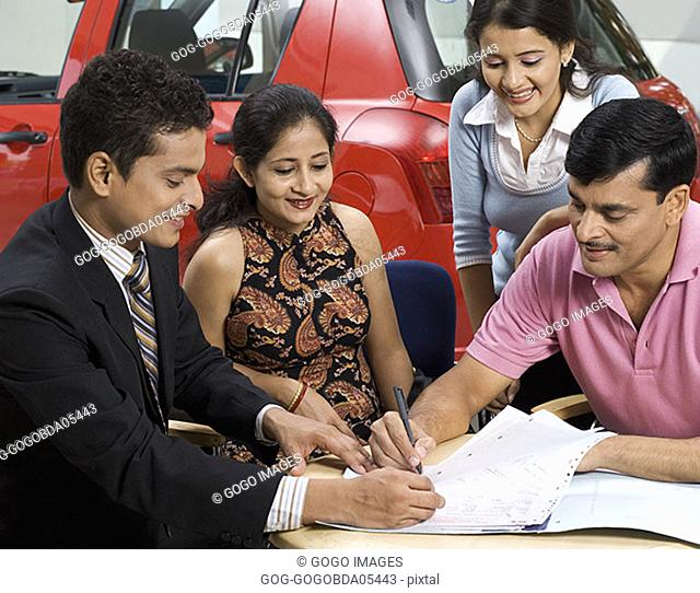 Family signing papers to buy new car