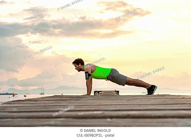 Side view of man on pier doing push-up, Mallorca, Spain