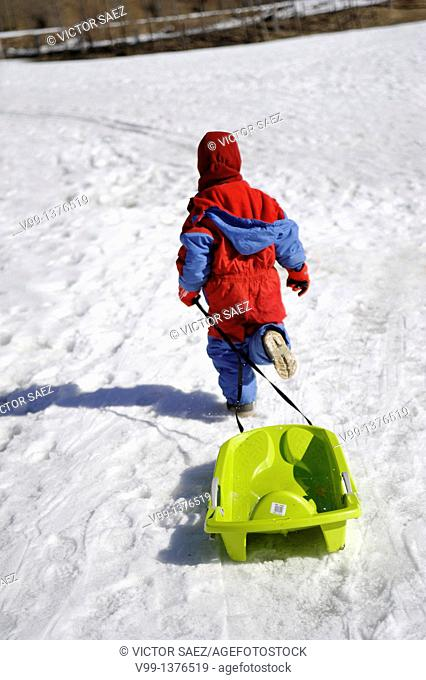 child running with a sled