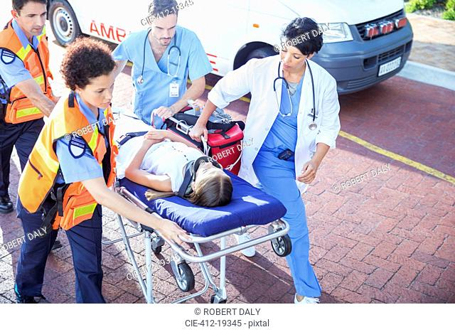 Doctor, nurse and paramedics wheeling patient on stretcher