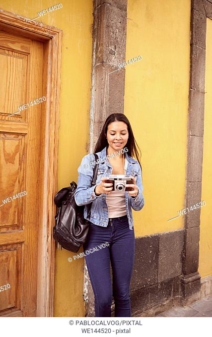 Pretty young girl leaning against a gray pillar smiling at her camera with old yellow buildings behind her in casual jeans and denim jacket