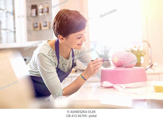 Female caterer finishing pink wedding cake in kitchen