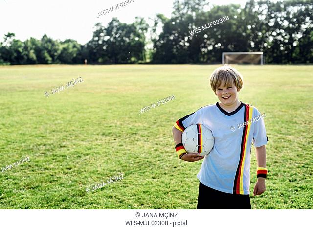 Boy wearing German soccer shirt, holding football