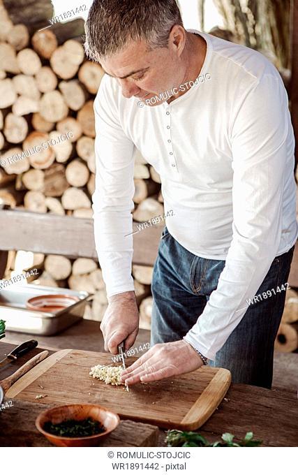Man cutting onions on cutting board