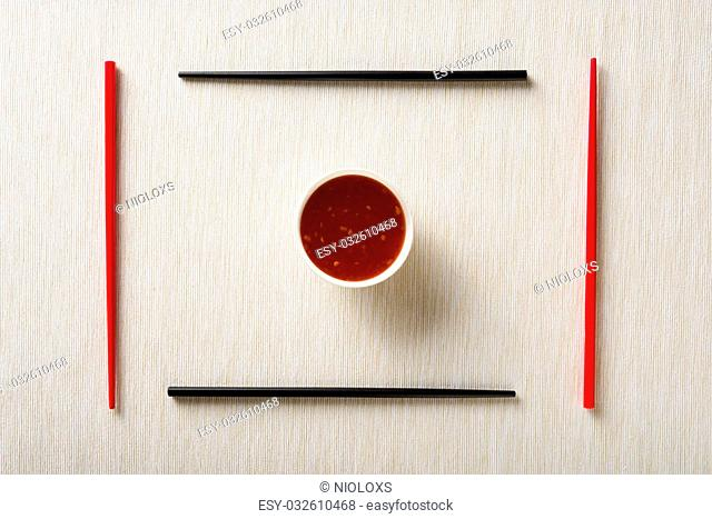 Chopsticks and bowl with sauce on table mat top view