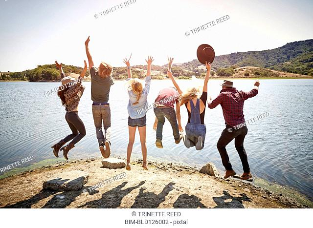 Friends jumping for joy at lakeside