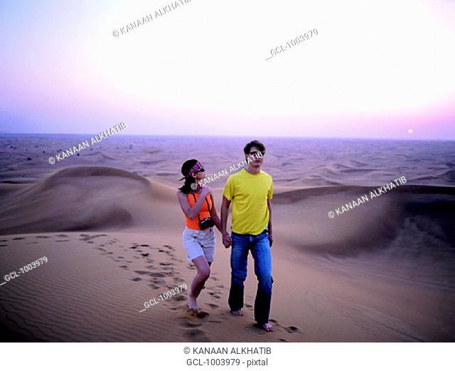 Western couple walking in the desert near Hatta, United Arab Emirates