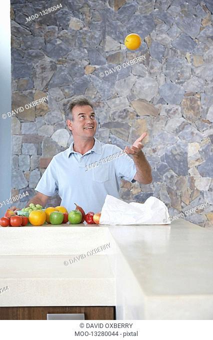 Mature man throwing orange into air standing at kitchen countertop