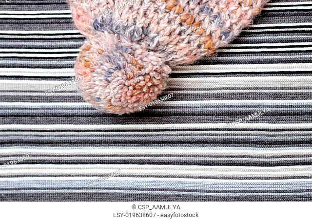 Woolen hat wit pompom on a knitting background