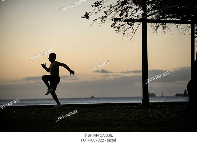 Full length of man jogging in park by sea at sunset