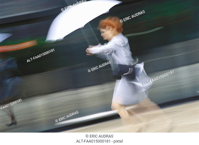 Businesswoman hurrying with umbrella