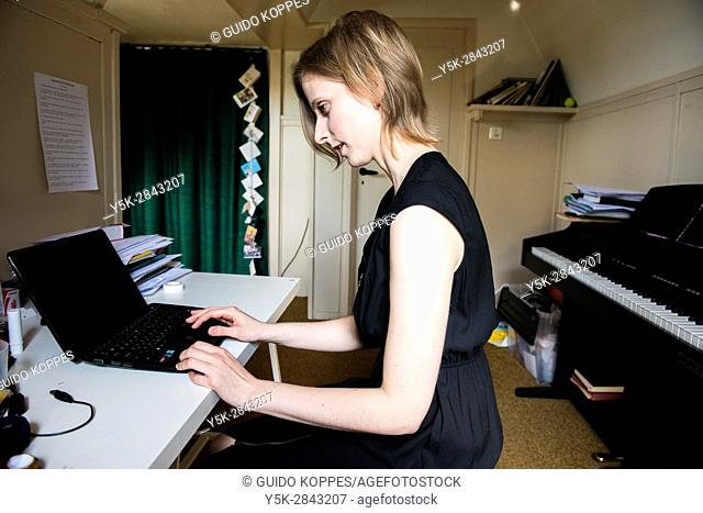 Tilburg, Netherlands. Classical singer and teacher working behind her computer inside her rehearsal room