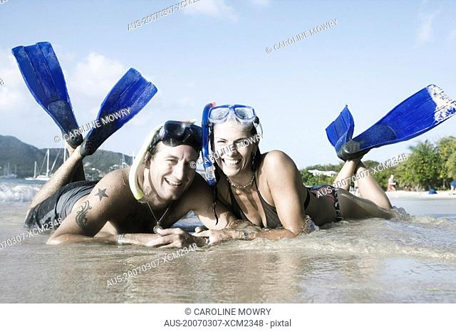 Portrait of a mid adult couple lying on the beach