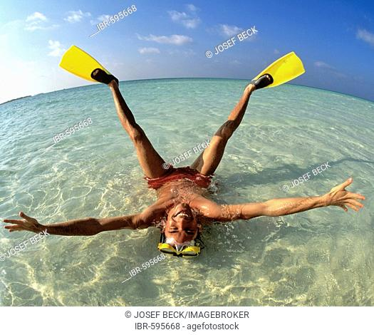 Young man wearing flippers laying in shallow water, vacation, Maldives, Indian Ocean