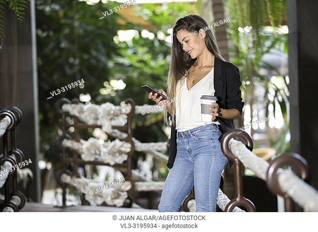 Trendy young woman in jacket holding paper cup of coffee and surfing smartphone in hotel
