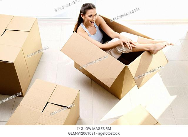 High angle view of a young woman laughing in a cardboard box