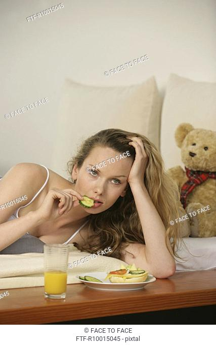 A young woman eats as she lies in her bed