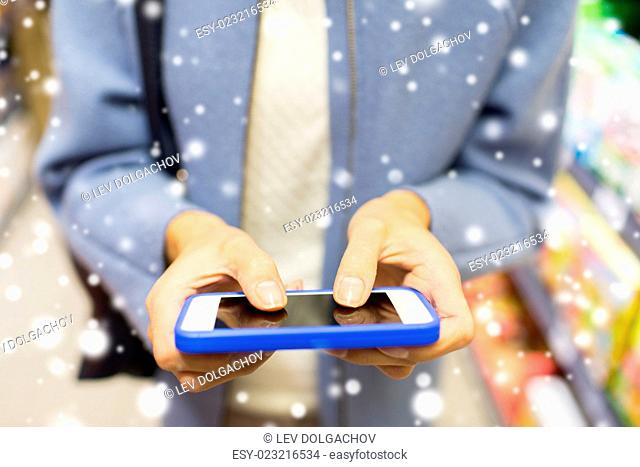 sale, shopping, consumerism and people concept - close up of woman with smartphone choosing and buying food in market over snow effect